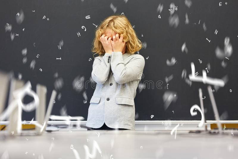 Enfant avec la dyslexie devant le tableau noir dans l'école primaire images stock