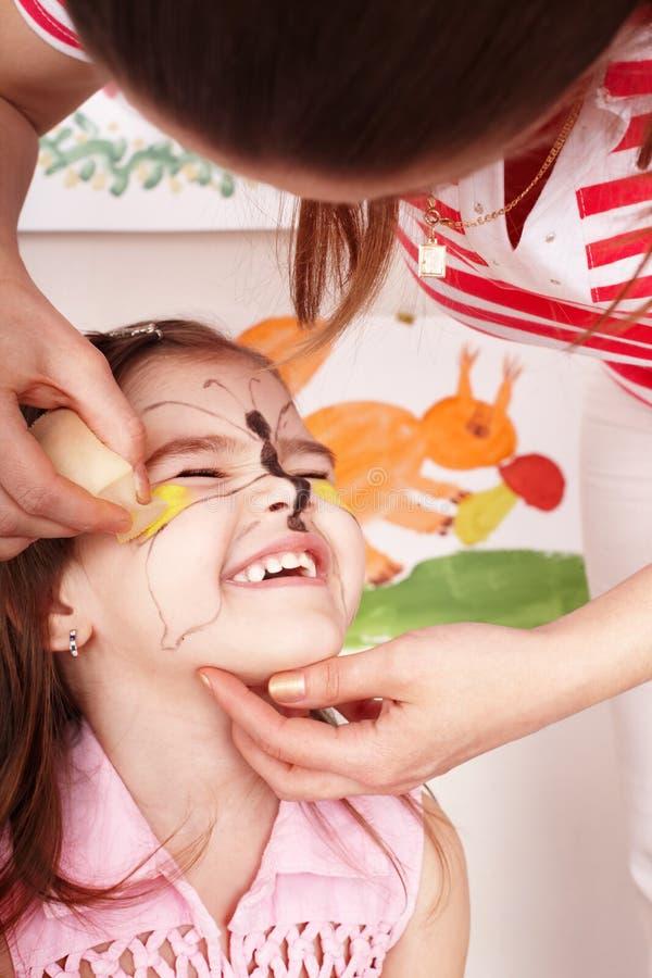 Enfant avec la peinture du visage dans la chambre de pièce. photographie stock