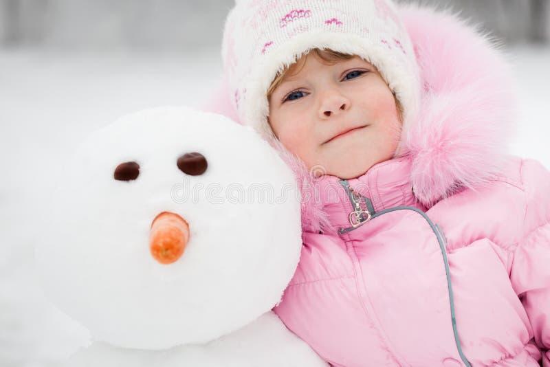 Enfant avec le bonhomme de neige images libres de droits