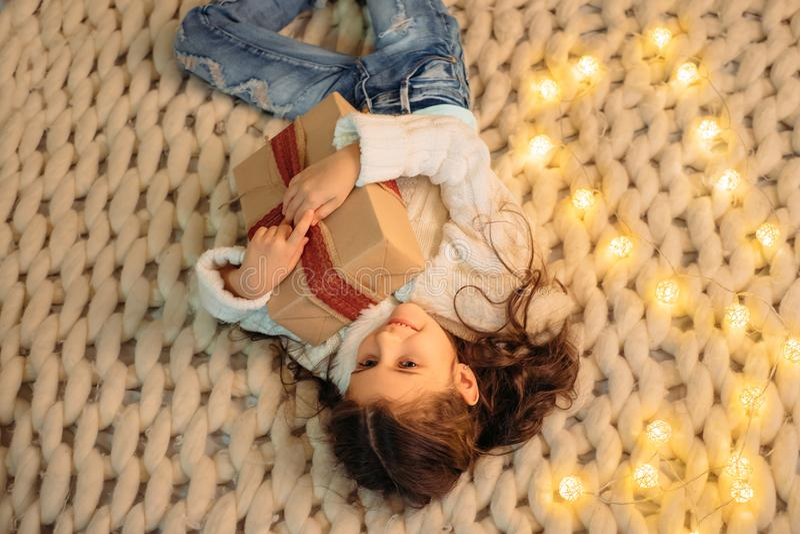 Enfant avec le cadeau de Noël sur le lit photos libres de droits