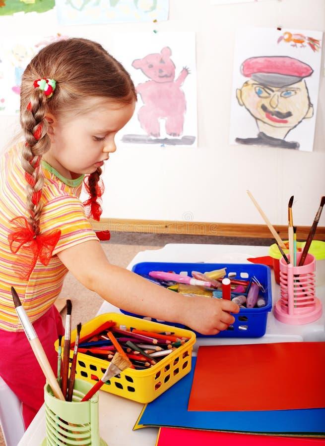 Enfant avec le crayon de couleur dans la chambre de pièce. photographie stock