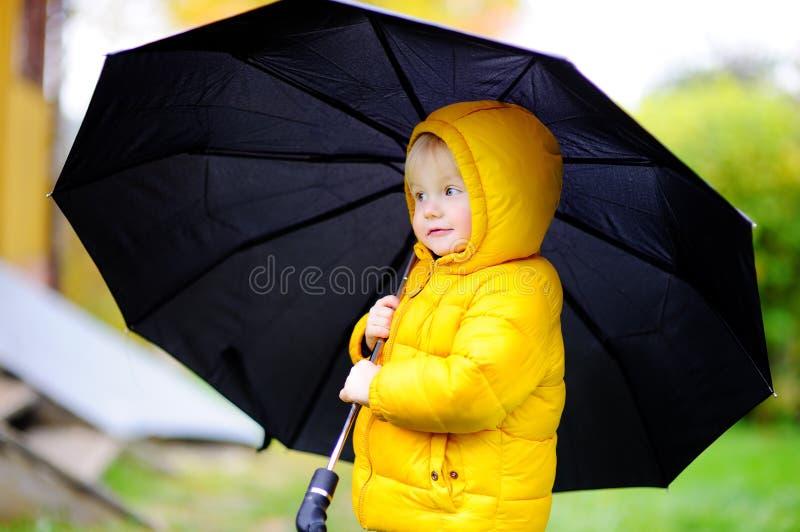 Enfant avec le grand parapluie noir sous la pluie photo libre de droits