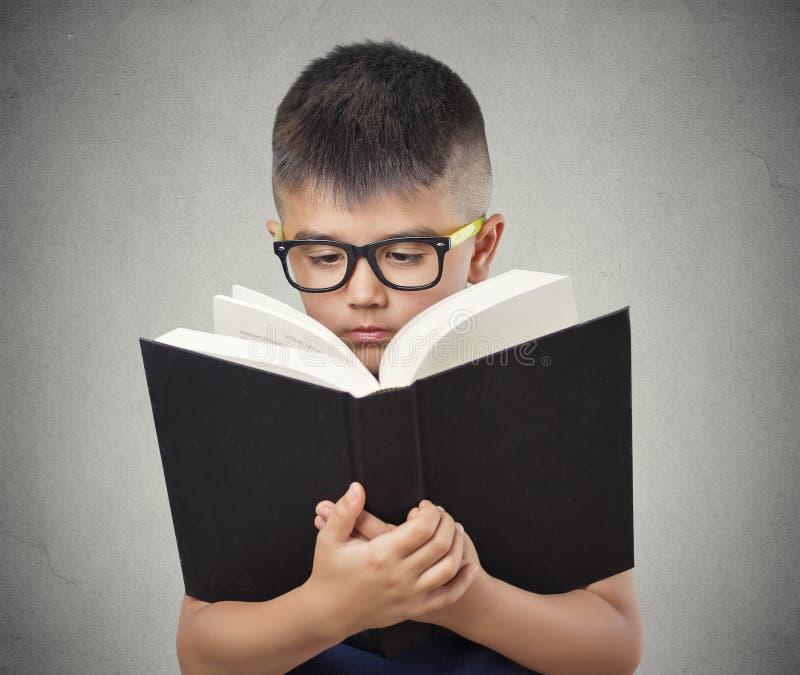 Enfant avec le livre de lecture en verre images stock