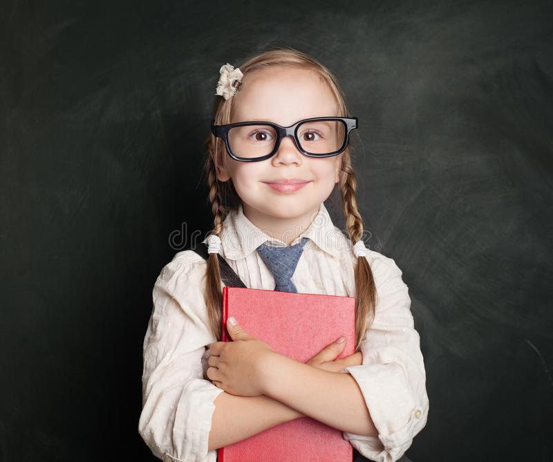 Enfant avec le livre Petite écolière dans des vêtements uniformes photos stock