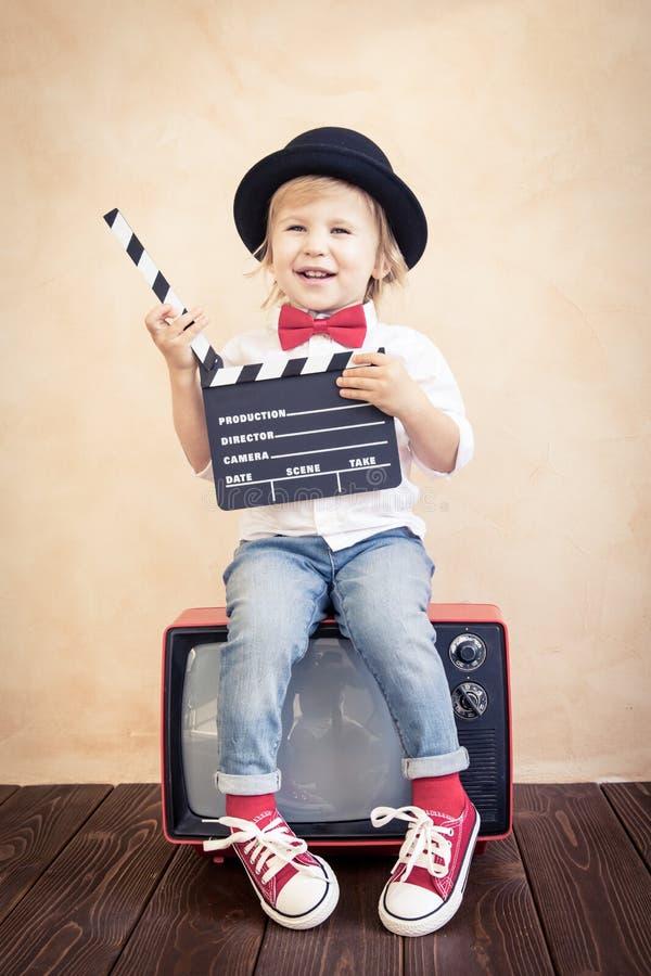 Enfant avec le panneau de clapet jouant ? la maison photographie stock