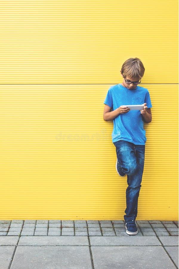 Enfant avec le téléphone portable se tenant près du mur jaune dehors photographie stock