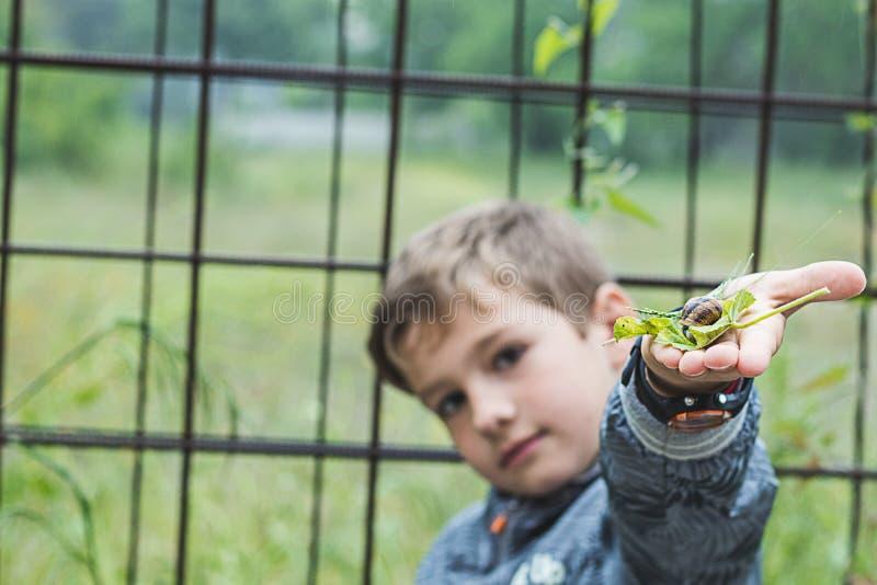 Enfant avec un escargot dans sa main images libres de droits