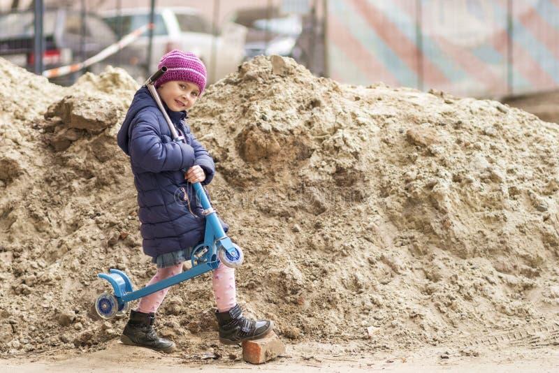 Enfant avec un scooter sur son ?paule photographie stock libre de droits