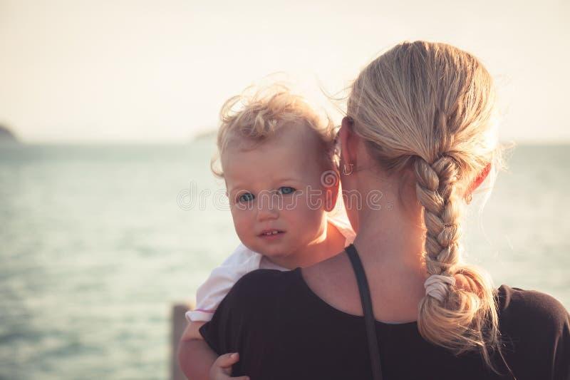 Enfant avec un sembler sincère étreignant sa mère s'asseyant sur ses mains et regardant l'appareil-photo image stock