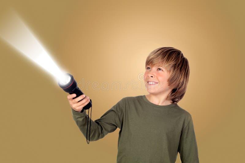 Enfant avec une lampe-torche recherchant quelque chose images libres de droits