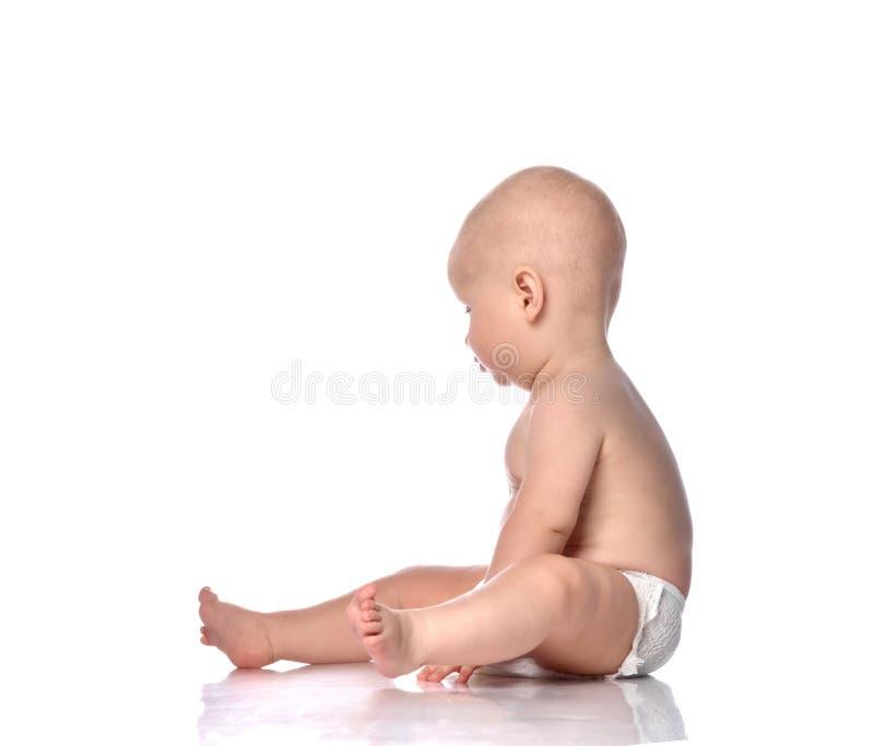 Enfant bébé petit garçon de retour assis dans la couche de derrière la vue arrière isolé sur un blanc photos libres de droits