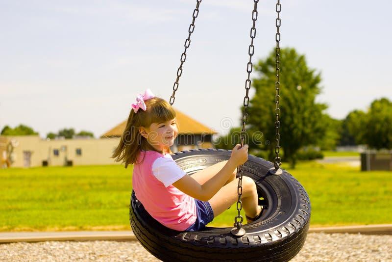 Enfant balançant sur une oscillation de pneu au stationnement images stock