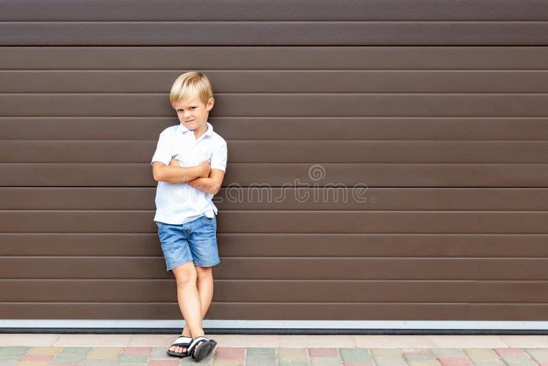 Enfant blond grincheux mignon dans les vêtements décontractés se tenant contre la porte brune de garage Garçon fâché d'enfant ave images stock