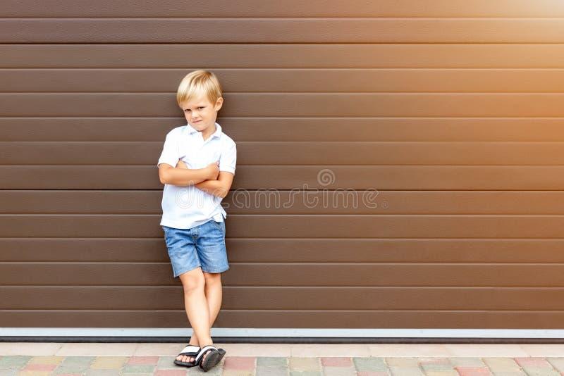 Enfant blond grincheux mignon dans les v?tements d?contract?s se tenant contre la porte brune de garage Gar?on f?ch? d'enfant ave photographie stock