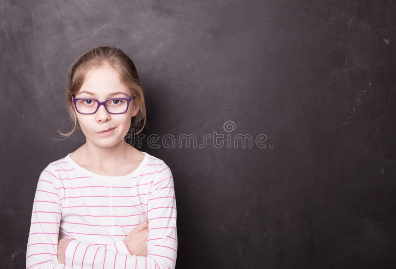 Enfant blond vilain de fille de chid au tableau noir de tableau images stock