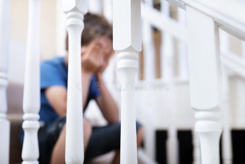 Enfant boulevers? de probl?me s'asseyant sur des escaliers photographie stock libre de droits