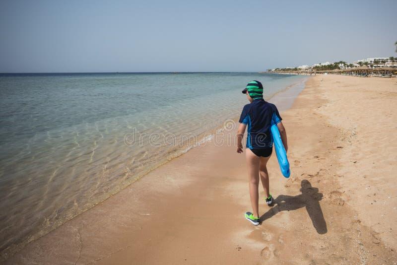 Enfant bronzé blanc mignon habillé dans des chaussures de maillot de bain, de chapeau et d'aqua photographie stock libre de droits