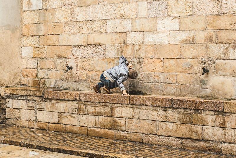 Enfant buvant d'une source d'eau images libres de droits