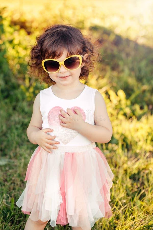 Enfant caucasien élégant adorable mignon dans la robe rose et des lunettes de soleil jaunes photographie stock libre de droits