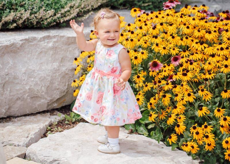 Enfant caucasien blanc adorable mignon de bébé dans la robe blanche se tenant parmi les fleurs jaunes dehors en parc de jardin photographie stock libre de droits