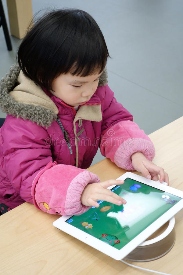 Enfant chinois jouant l'ipad photos stock
