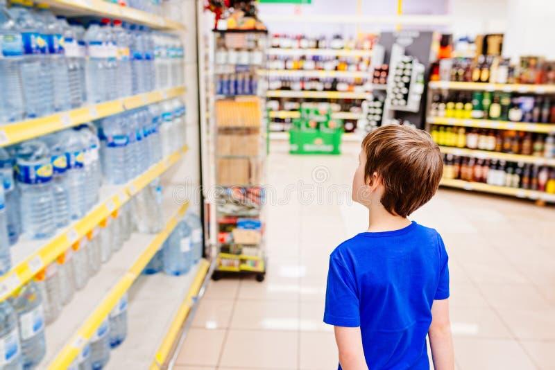 Enfant choisissant l'eau minérale mis en bouteille photos stock