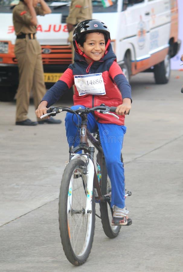 Enfant conduisant la bicyclette avec enthousiasme dans la conduite de jour de république images libres de droits