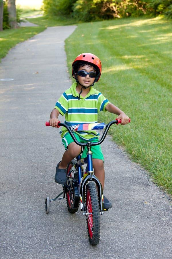 Enfant conduisant son vélo sur un journal faisant du vélo image libre de droits