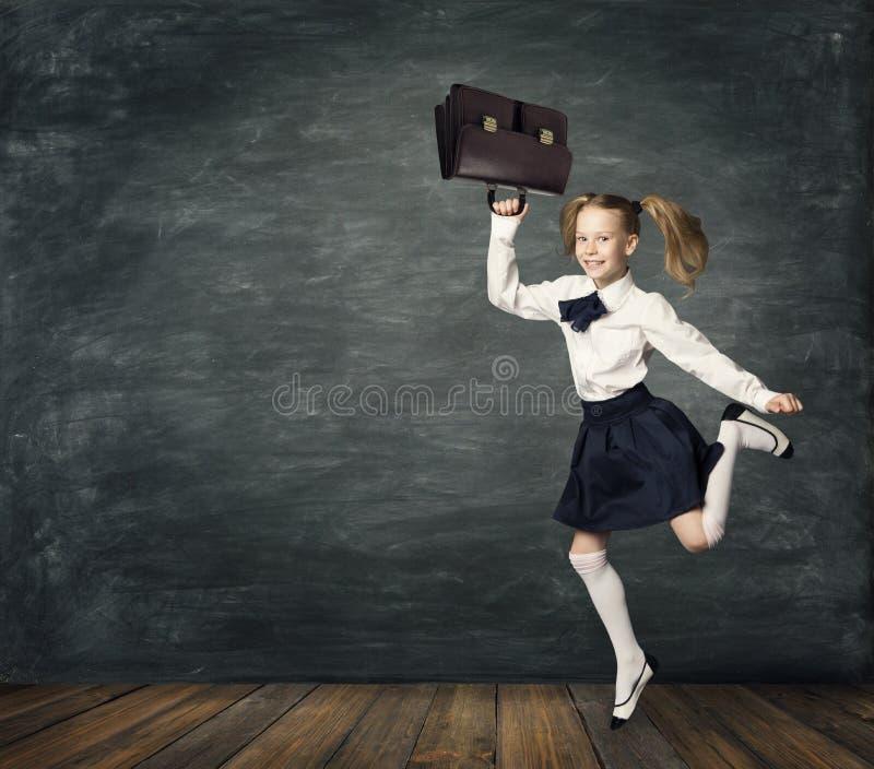 Enfant courant à l'école, enfant de fille sautant, tableau noir de salle de classe photos stock