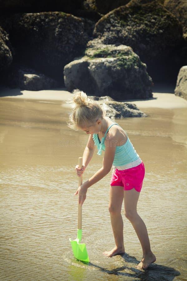 Enfant creusant dans le sable avec une pelle photos stock