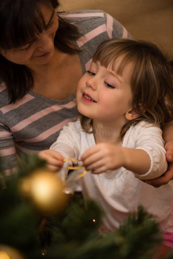 Enfant décorant l'arbre de Noël avec la mère photos stock