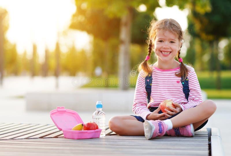 Enfant d'écolière mangeant des pommes de déjeuner à l'école photo stock