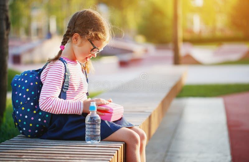 Enfant d'écolière mangeant des pommes de déjeuner à l'école photographie stock libre de droits