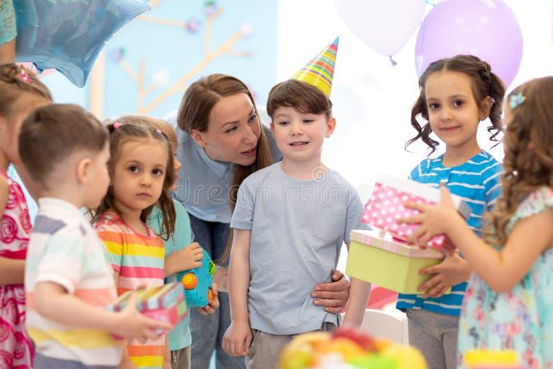 Enfant d'anniversaire préscolaire recevant des cadeaux d'amis images libres de droits