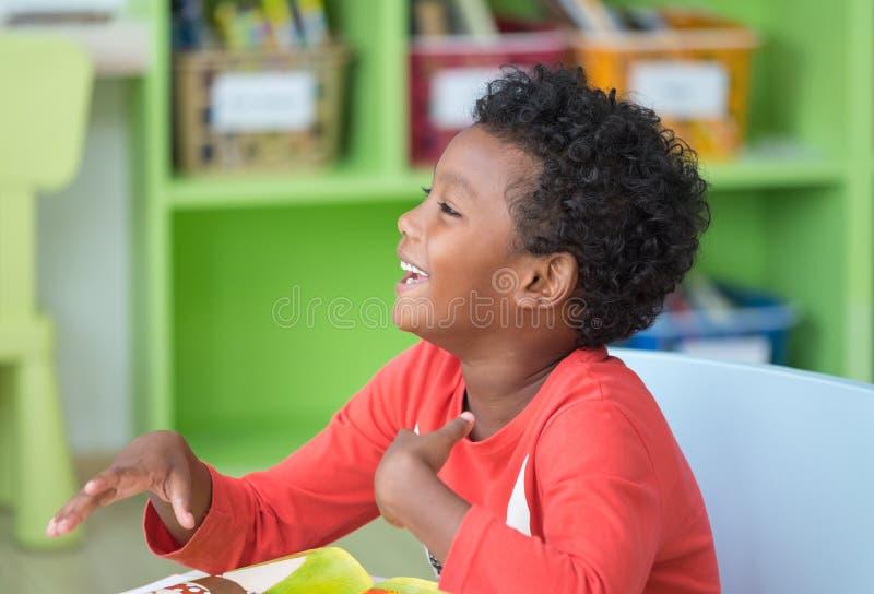 Enfant d'appartenance ethnique d'afro-américain souriant à la bibliothèque dans la salle de classe d'école maternelle de jardin d images libres de droits