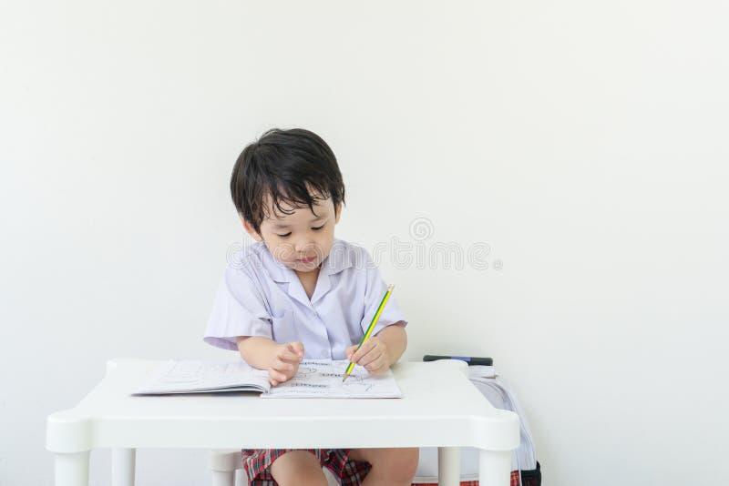 Enfant d'asain de plan rapproché se reposant pour faire des devoirs après école sur le fond blanc de mur photos stock