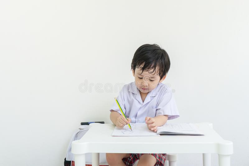 Enfant d'asain de plan rapproché se reposant pour faire des devoirs après école sur le fond blanc de mur images libres de droits