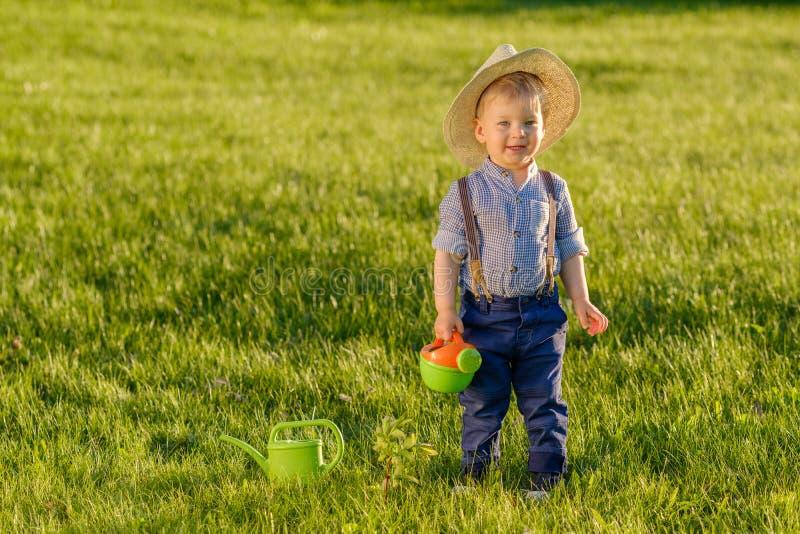 Enfant d'enfant en bas âge dehors Un chapeau de paille de port de bébé garçon an utilisant la boîte d'arrosage image libre de droits