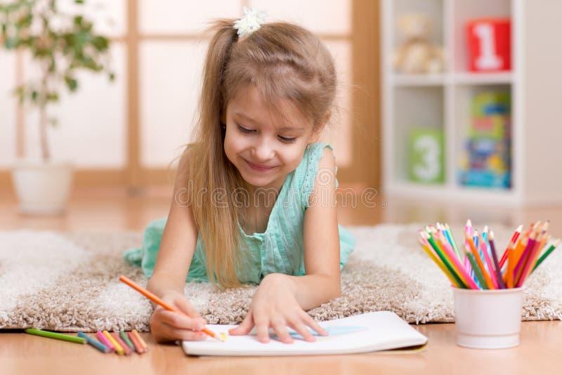 Enfant d'enfant de petite fille d'enfant dessinant à la maison image stock