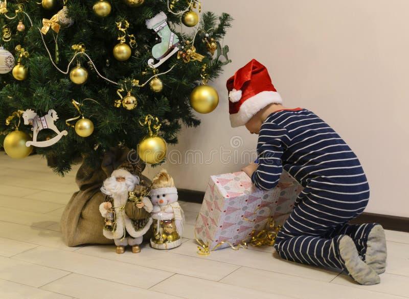 Enfant dans des pyjamas trouvant le cadeau sous l'arbre de Noël photo stock