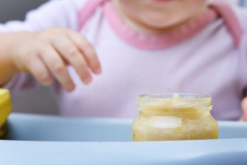 Enfant dans la cuisine mangeant de la purée de fruit, profondeur de champ, foyer sélectif photos stock