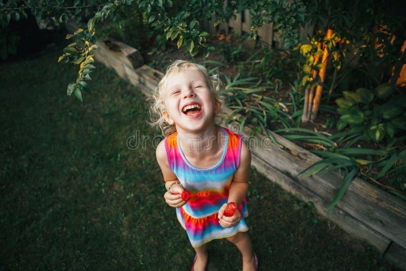 Enfant dans la robe colorée fonctionnant dans le jardin sur l'arrière-cour à la maison photographie stock libre de droits