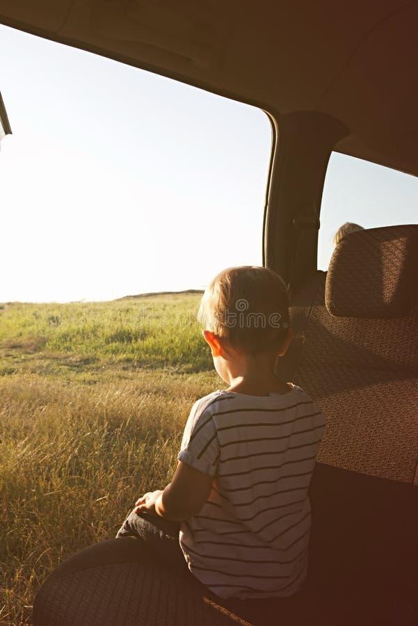 Enfant dans la voiture et examinations la distance image libre de droits