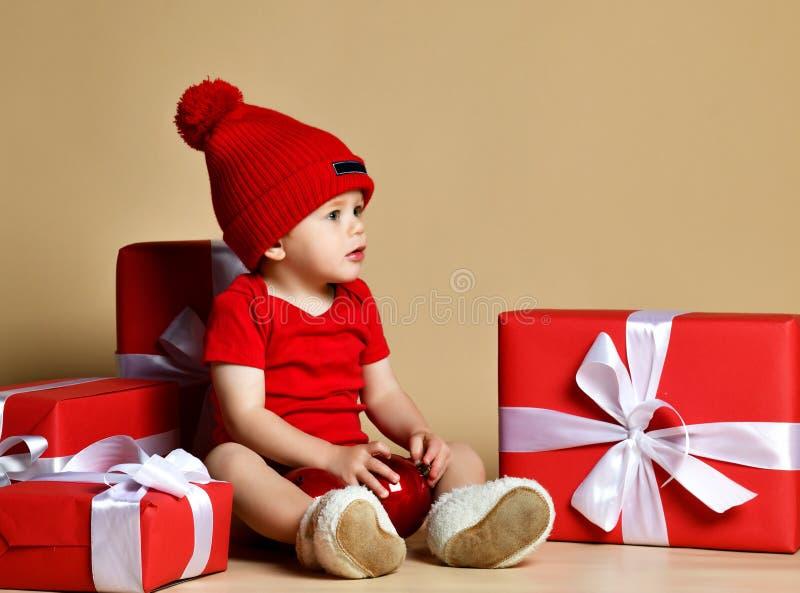 Enfant dans le chapeau rouge avec des piles de boîtes actuelles autour de se reposer sur le plancher photographie stock