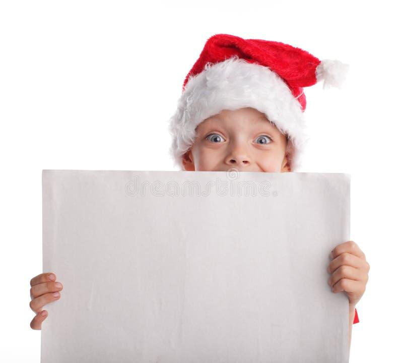 Enfant dans un chapeau de Noël et la forme dans des mains images stock