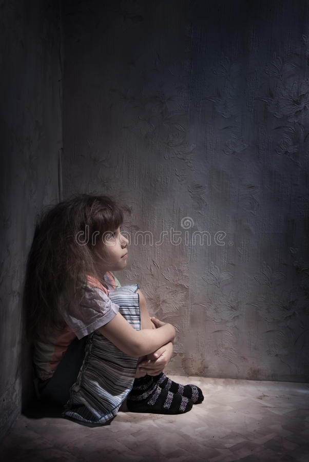 Enfant dans un coin foncé image libre de droits