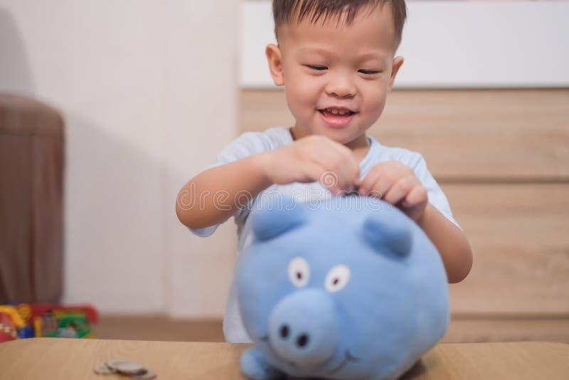 Enfant de bébé garçon d'enfant en bas âge mettant la pièce de monnaie thaïlandaise dans la tirelire bleue photographie stock libre de droits