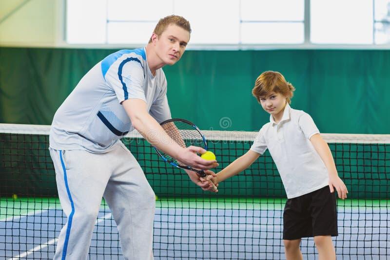 Enfant de enseignement d'instructeur ou d'entraîneur comment jouer au tennis sur une cour d'intérieur photos stock