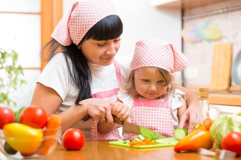 Enfant de enseignement de mère faisant la salade dans la cuisine Maman et enfant coupant le légume sur la planche à découper avec image libre de droits