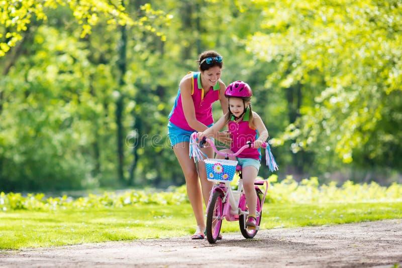 Enfant de enseignement de mère pour monter un vélo photos stock